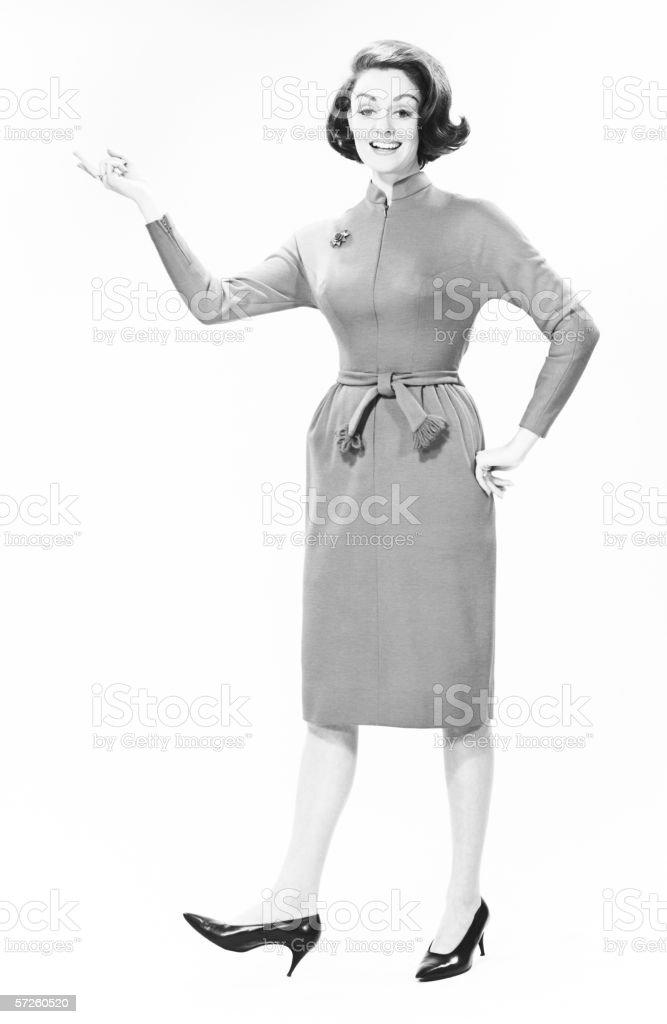 Elegant woman standing in studio, gesturing, (B&W), portrait stock photo
