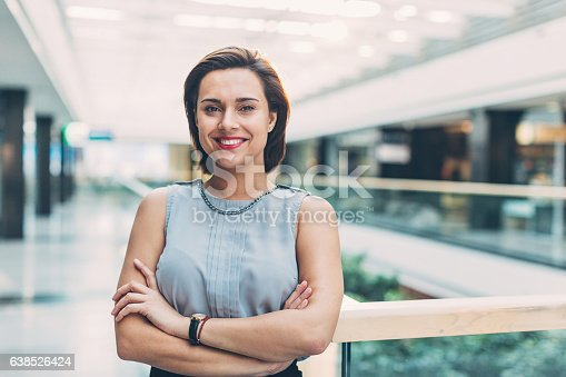 istock Elegant woman standing inside of business building 638526424