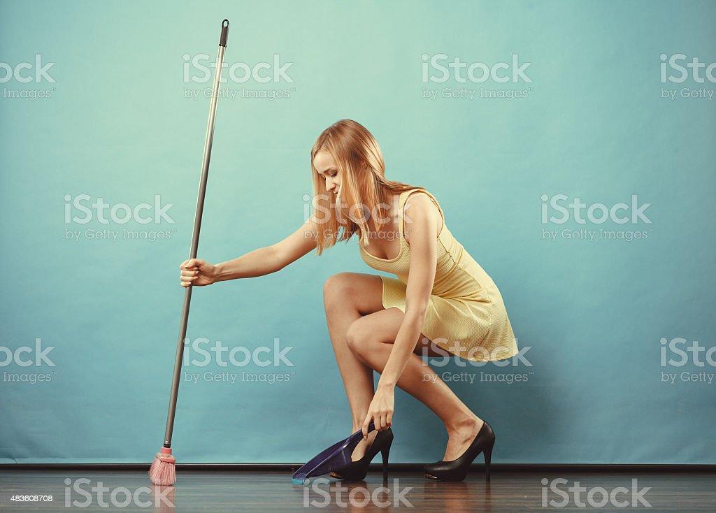Elegant woman sweeping floor with broom stock photo