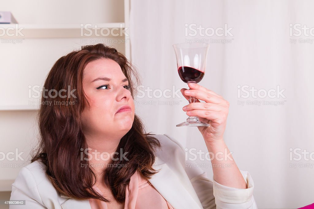 Elegant woman tests a glass of red wine stock photo