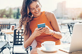 Attractive woman with smart phone and laptop sitting outdoors in cafe