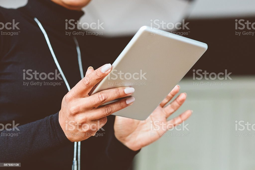 Elegant woman using digital tablet, close up of hands Elegant woman using a digital tablet at home, close up of hands, unrecognizable person. Adult Stock Photo