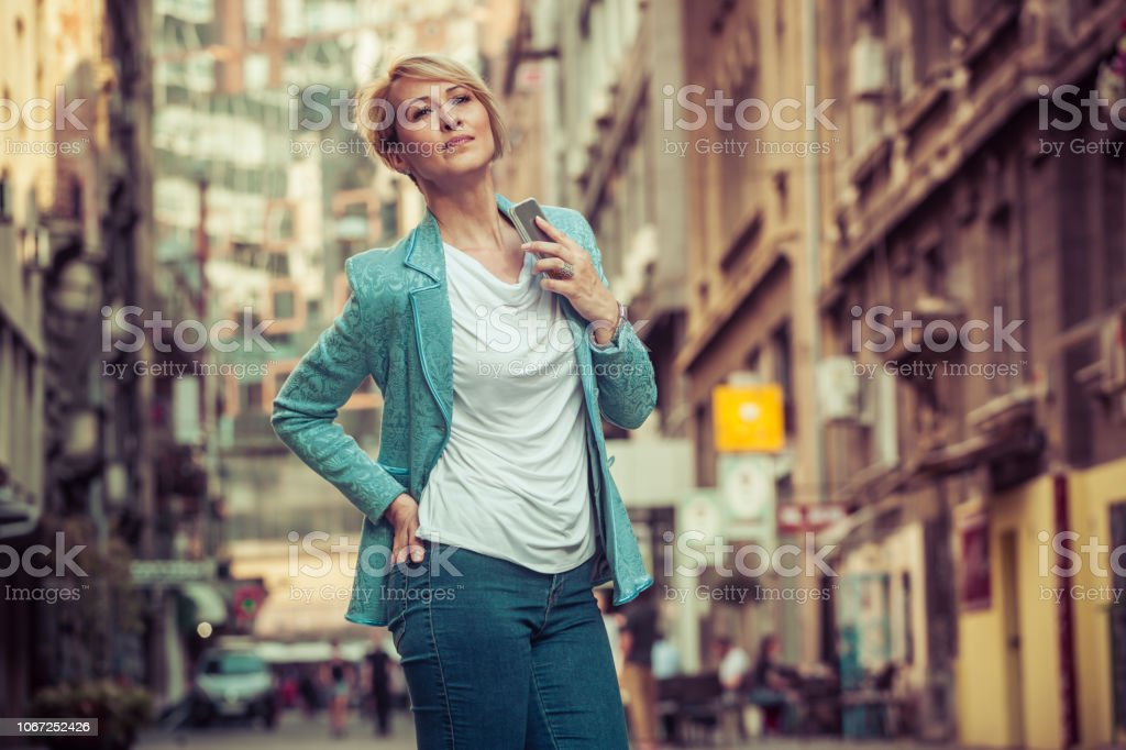 Elegant woman waiting for someone in the street stock photo