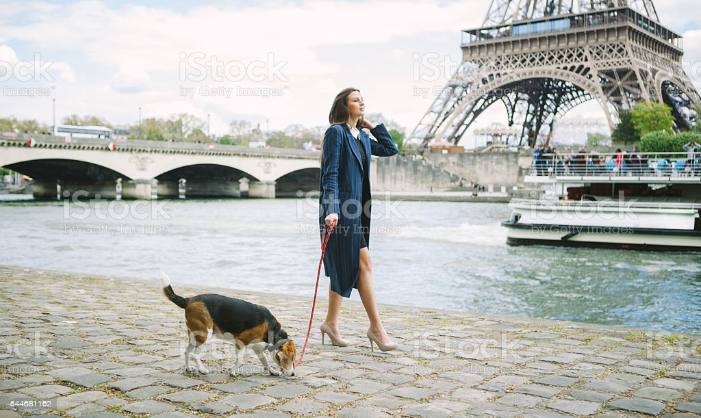 Elegant Woman Walking Her Dog By The Riverside stock photo