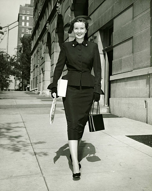 elegant woman walking on sidewalk, (b&w) - 1940s style stock photos and pictures