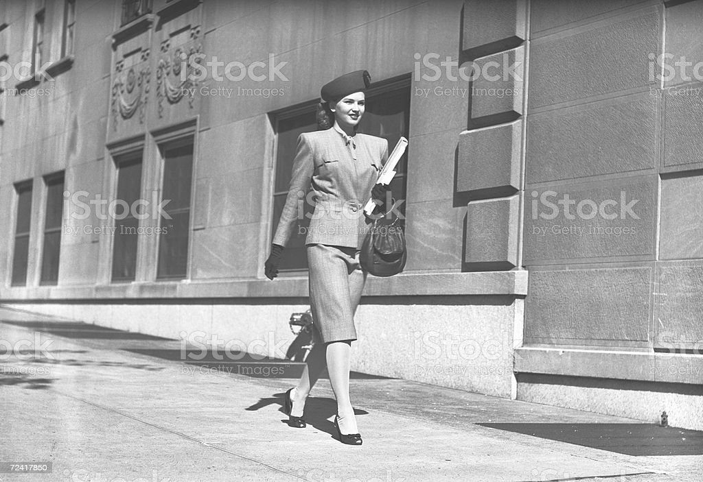 Elegant woman walking on sidewalk, (B&W) stock photo