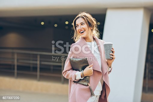 Elegant young woman walking on the sidewalk at urban setting and looking back.