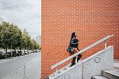 istock elegant woman walking up stairs in modern district in Berlin 1248460047