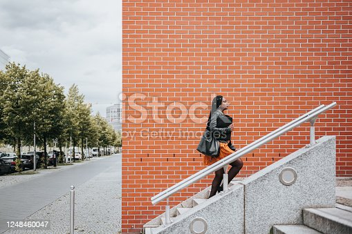 elegant young black business woman walking up stairs at Potsdamer Platz in Berlin