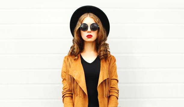 elegante frau trägt ein retro-eleganten hut, sonnenbrille, braune jacke und schwarze handtasche kupplung auf grauem hintergrund - bedruckte leggings stock-fotos und bilder