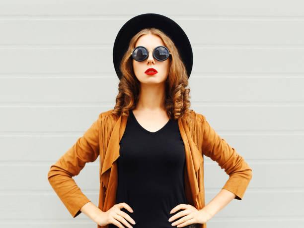 elegante frau mit schwarzen hut, sonnenbrille und jacke über urbane grauen hintergrund - bedruckte leggings stock-fotos und bilder