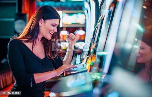 Elegant woman playing on a slot machine