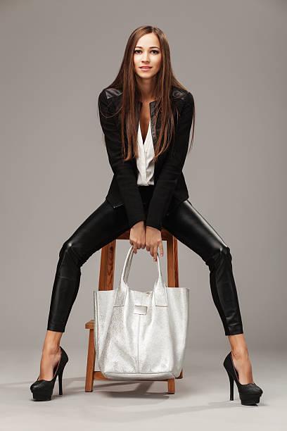 elegante frau mit mode-tasche - leder leggings stock-fotos und bilder