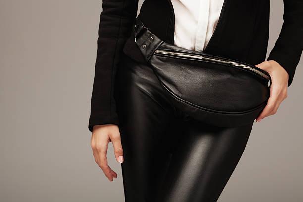 elegante frau mit einem leder-gürteltasche - leder leggings stock-fotos und bilder