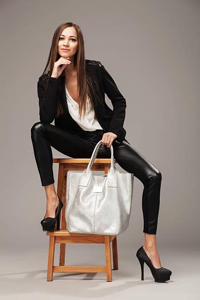 elegante frau mit einem silver-tasche - leder leggings stock-fotos und bilder