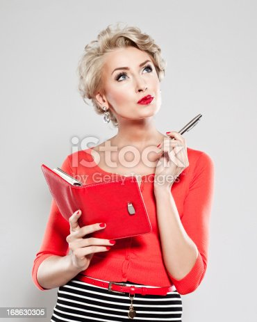 Portrait of penisive woman holding a calendar and pen in her hands, looking up.