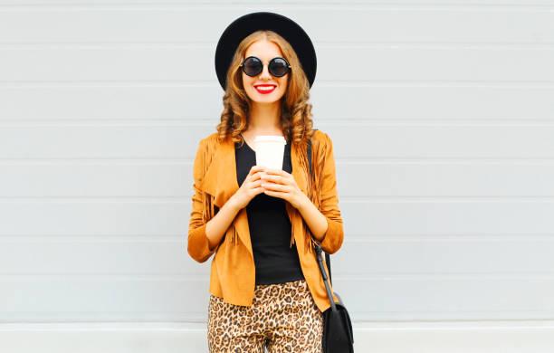 elegante dame mit kaffeetasse tragen retro elegante hut, sonnenbrille, braune jacke und schwarze handtasche in grau hinterlegt - bedruckte leggings stock-fotos und bilder