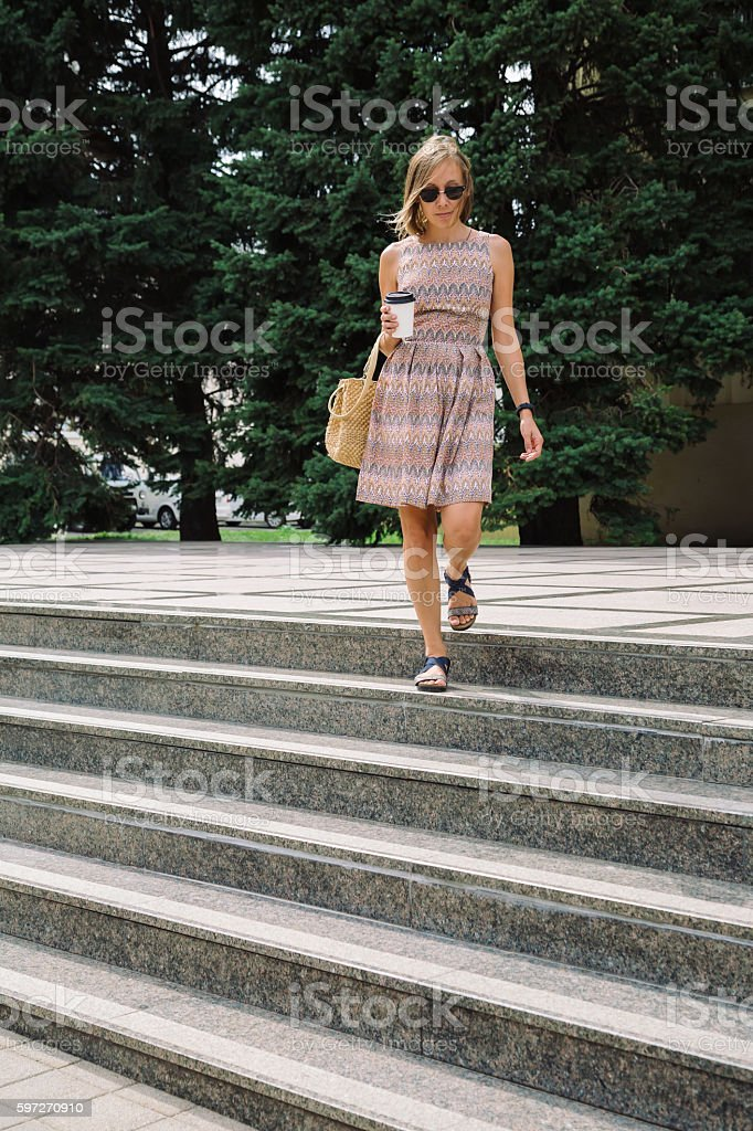 Elegant woman with coffee to go walking down the steps photo libre de droits