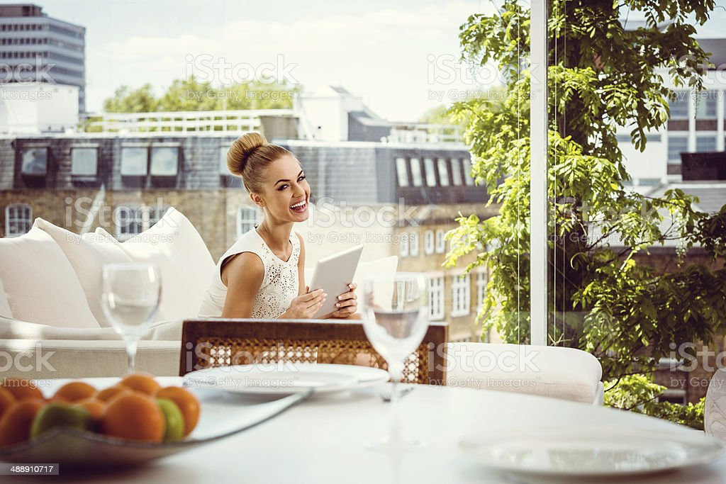 Elegant woman with digital tablet Elegant woman sitting on sofa in posh apartment with a digital tablet, dining table in the foreground. 20-24 Years Stock Photo