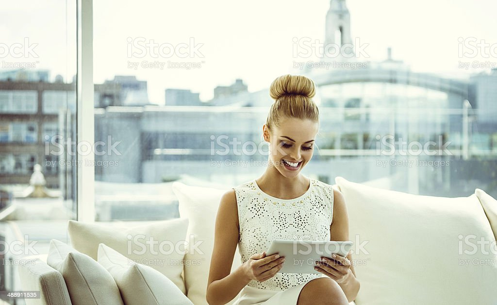 Elegant woman with digital tablet Elegant young woman sitting on sofa in an apartment and using a digital tablet with cityscape in the background.  20-24 Years Stock Photo