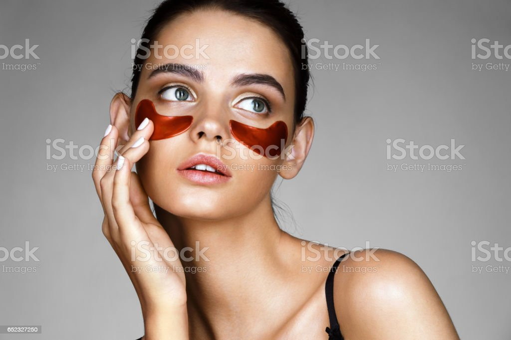 Elegant woman with eye patches showing an effect of perfect skin. – Foto