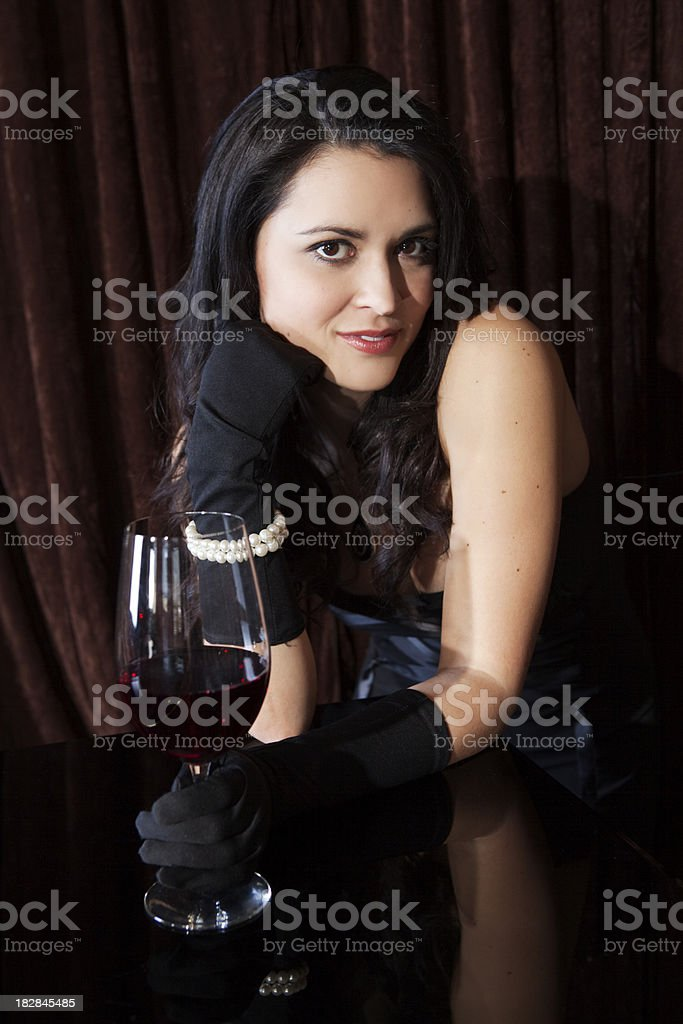 Elegant woman with gloves enjoying glass of wine at piano stock photo