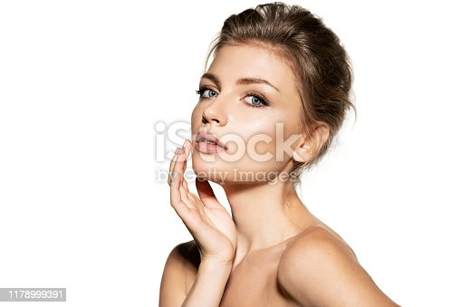 Modern model with bare shoulders and natural makeup concerns perfect skin clean hands standing on a white background.
