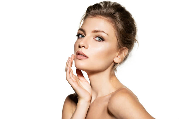 Elegant woman with natural beauty, she touches her well-groomed face and looks into the camera stock photo