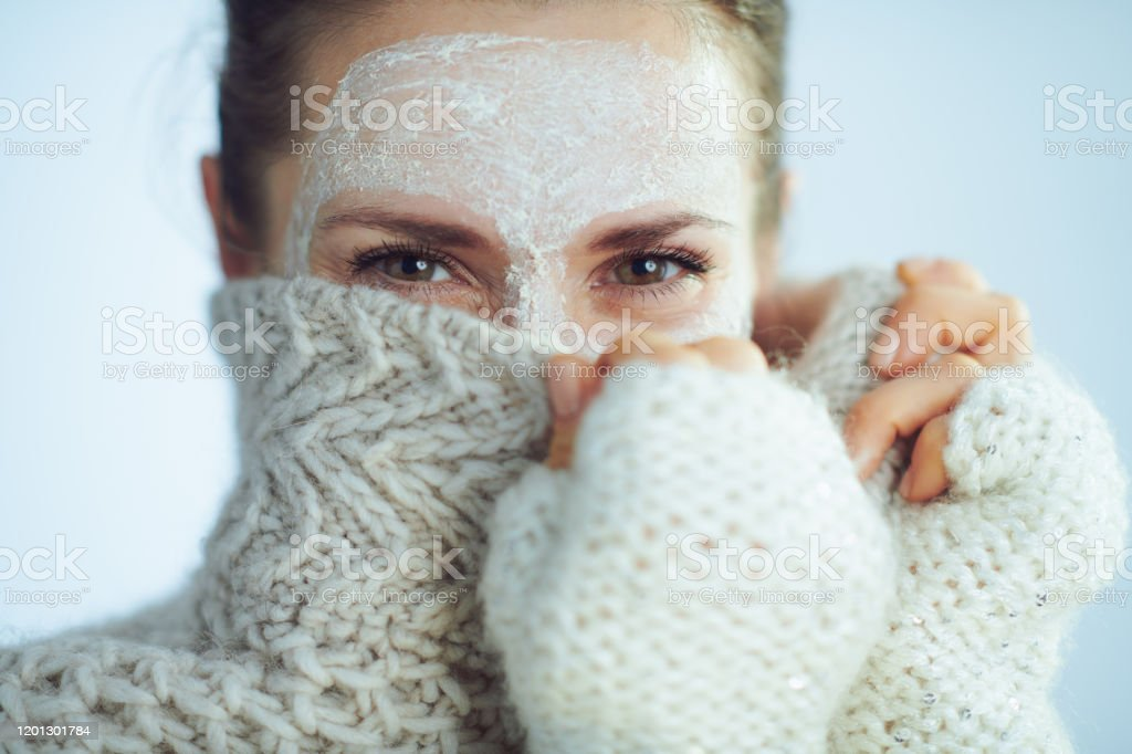 elegant woman with white facial mask hiding behind clothes elegant woman in roll neck sweater and cardigan with white facial mask hiding behind clothes on winter light blue background. Adult Stock Photo