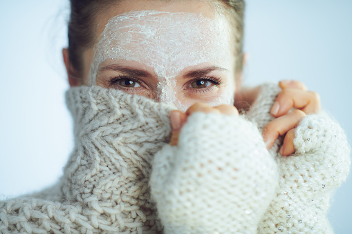 Elegant Woman With White Facial Mask Hiding Behind Clothes Stock Photo - Download Image Now