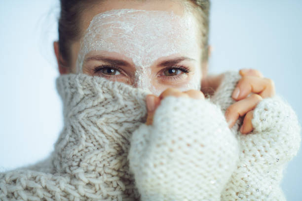 elegant woman with white facial mask hiding behind clothes stock photo