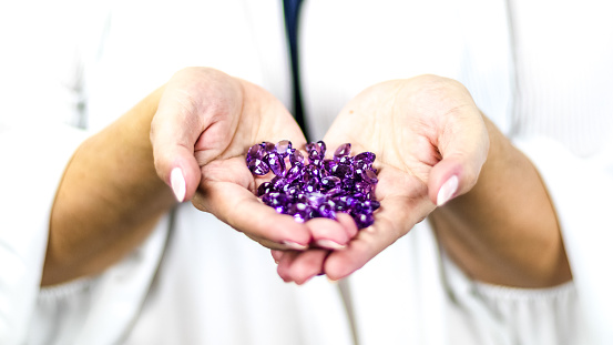 Elegant woman's hands hold many precious stones. Purple amethysts with beautiful color and shine.