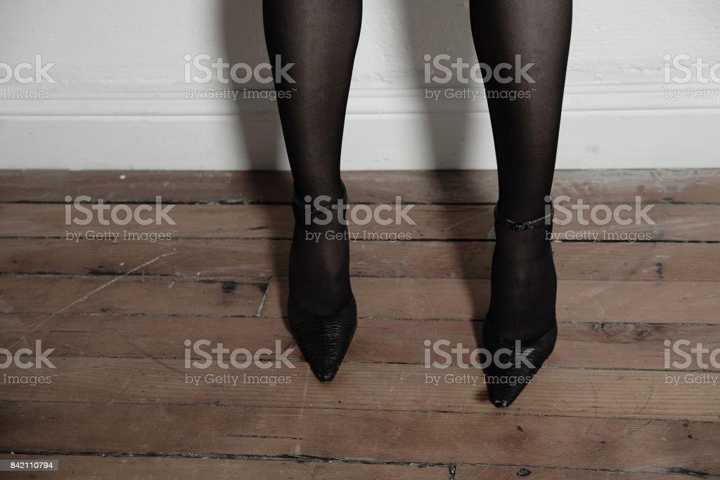 Elegant woman\'s legs in stocking and high heels with white copy space