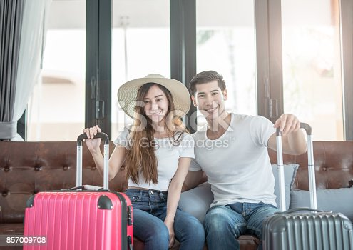 842907838 istock photo Elegant young Asian couple sitting waiting with baggage. vacation and traveler concept 857009708