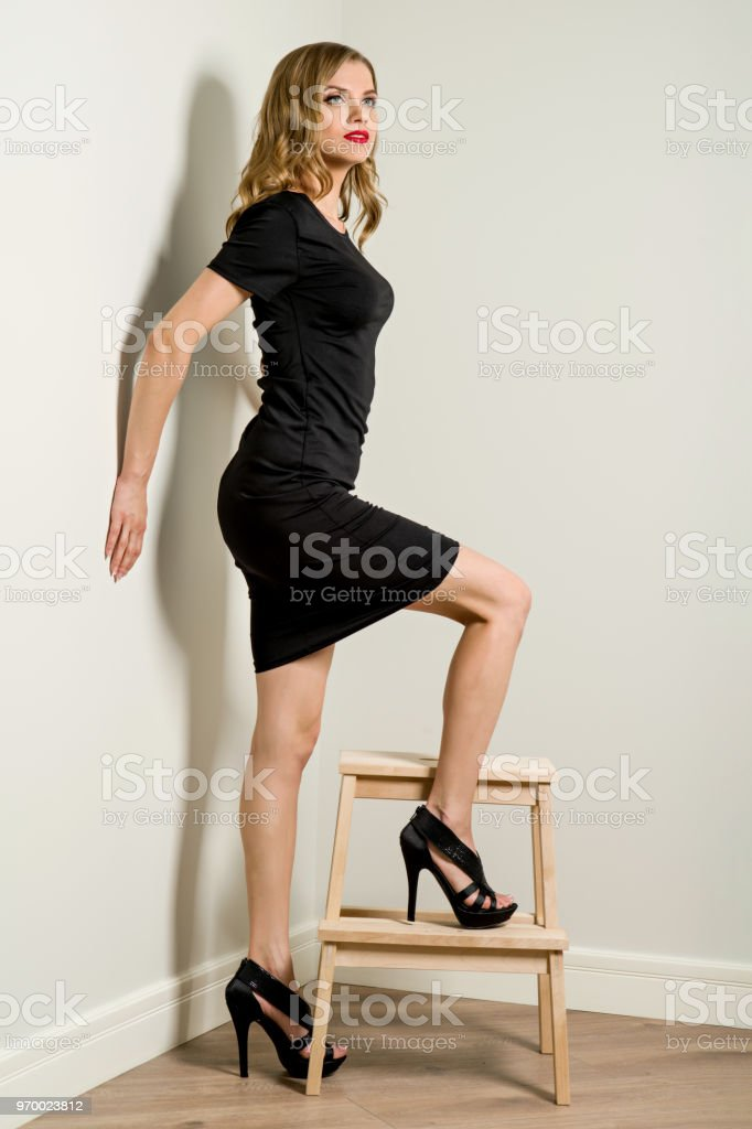 Elegant Young Business Woman Blond In Black Dress Poses Beside A