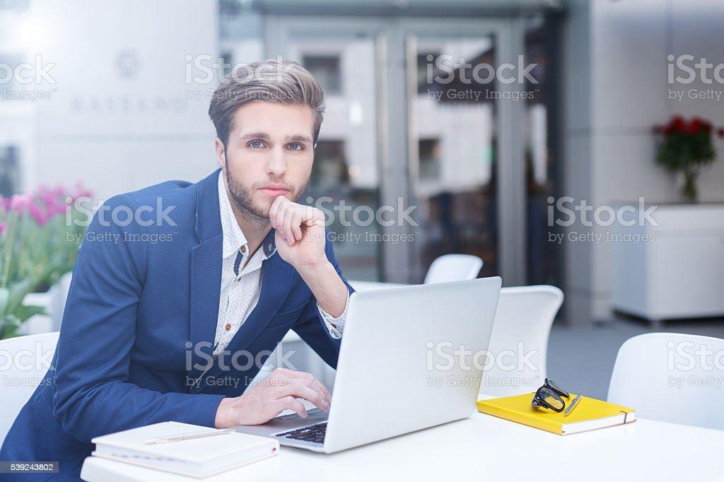 Elegante joven hombre de negocios está trabajando con el ordenador foto de stock libre de derechos