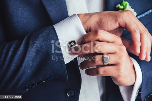 elegant young fashion man fixing cufflinks