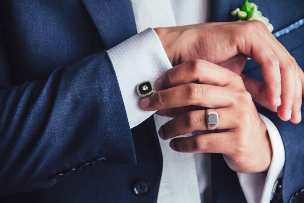 elegant young fashion man fixing cufflinks stock photo