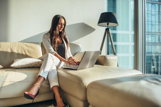 elegante jonge vrouwelijke zakenvrouw met behulp van een laptop zitting op een sofa thuis - woman very rich stockfoto's en -beelden