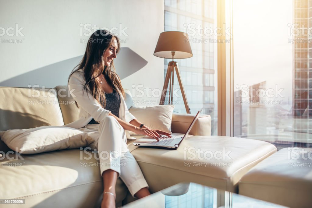 Elegant young female business woman using a laptop sitting on a sofa at home stock photo
