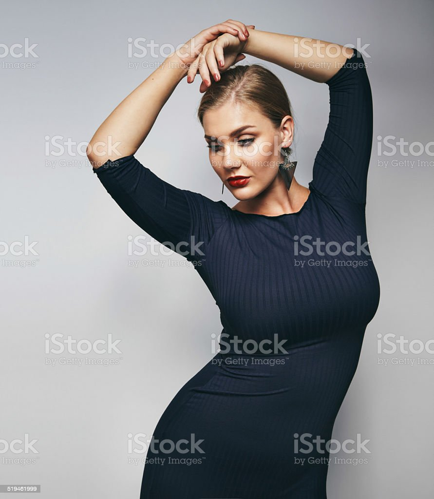Elegant young lady posing on grey background stock photo