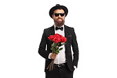 istock Elegant young man holding a bunch of red roses 1157628887