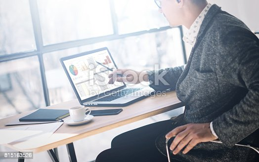 istock Elegant young man in eyeglasses working at office on laptop while sitting at the wooden table.Businessman anazyle graphs and diagramm on notebook screen.Horizontal, blurred background. 815163526