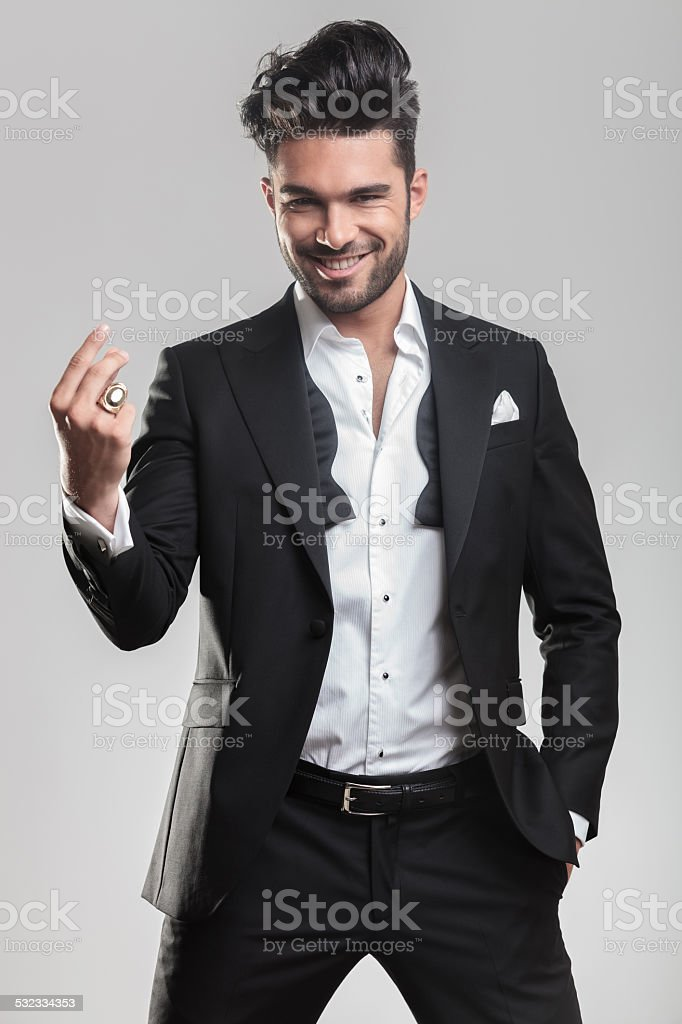 Elegant young man in tuxedo snapping his finger stock photo