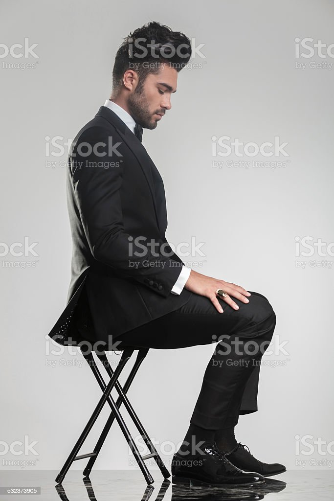 elegant young man sitting on a stool looking down stock photo