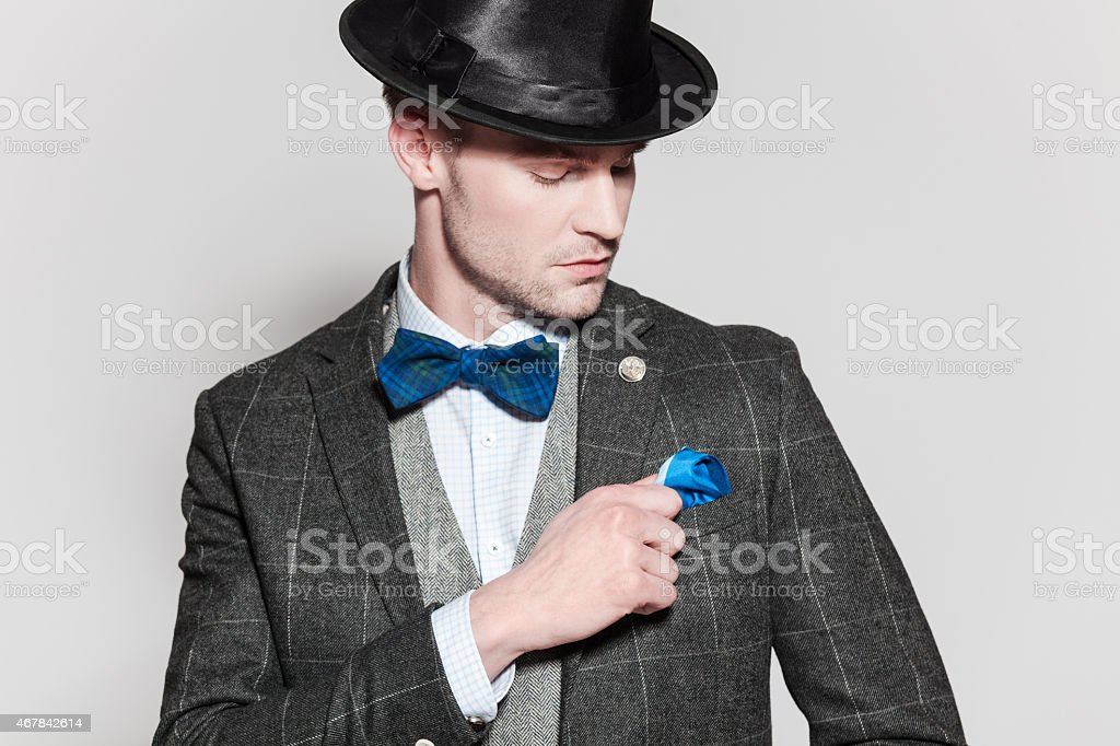 Elegant young man wearing tweed jacket, bow tie and bowler stock photo