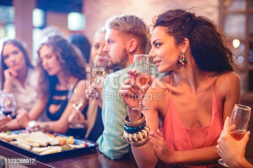 Elegant young woman at the bar holding champagne flute and looking over shoulder at group of people