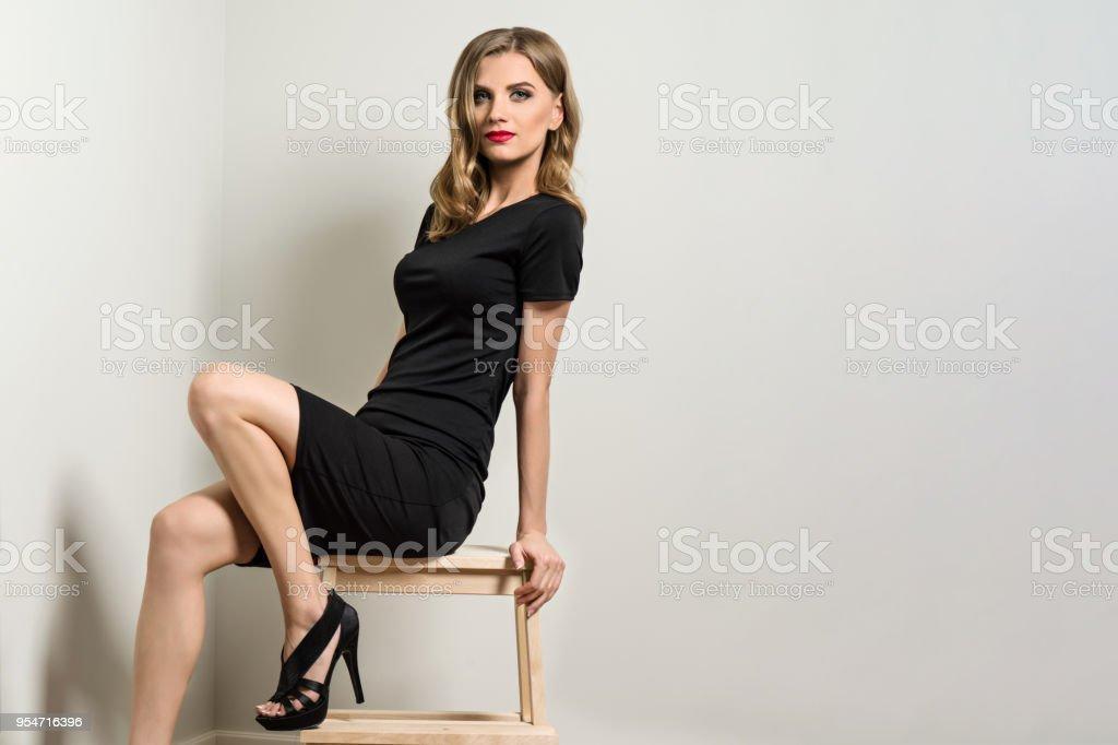 9a3440f2a Rubia Elegante Joven En Vestido Negro Foto de stock y más banco de ...
