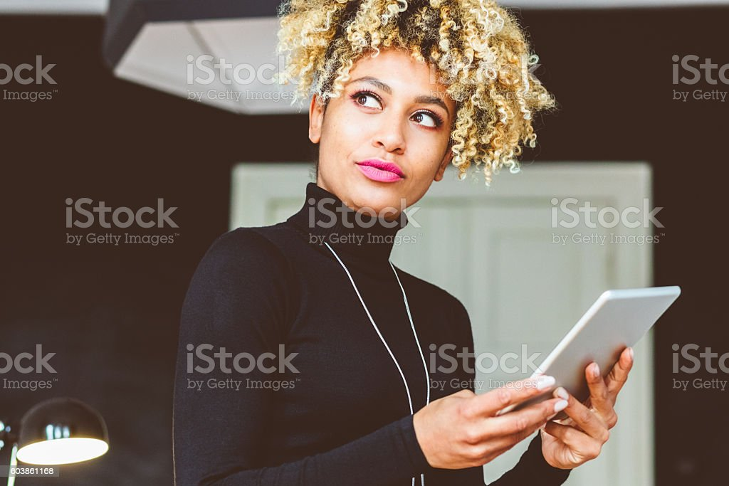 Elegant young woman holding digital tablet Beautiful elegant afro american young woman using a digital tablet in an office or at home Adult Stock Photo