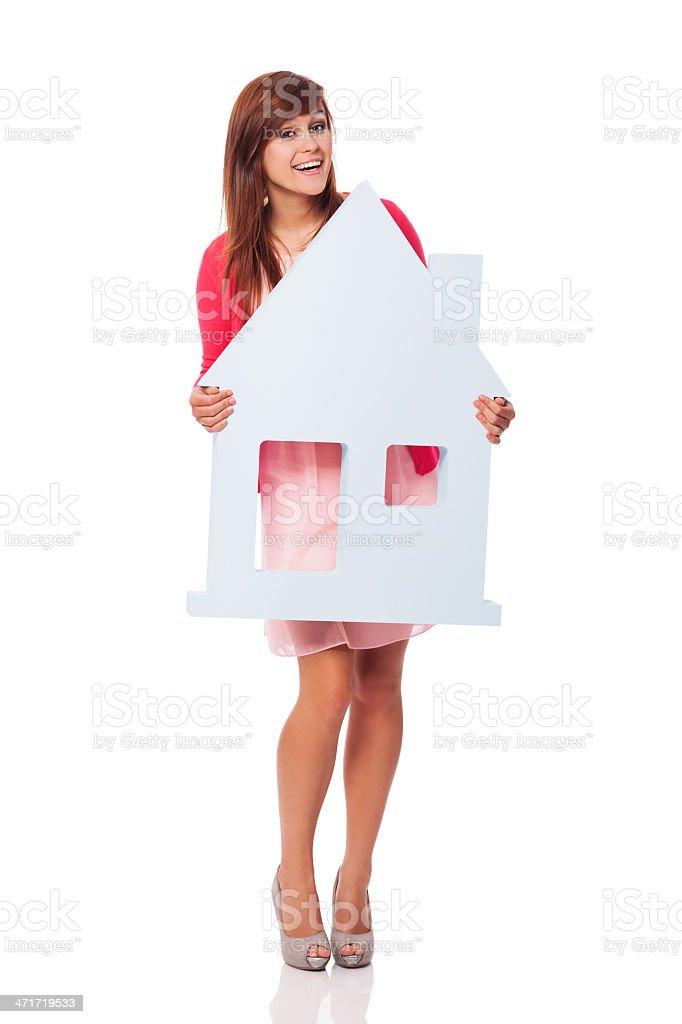 Elegant young woman holding house sign royalty-free stock photo